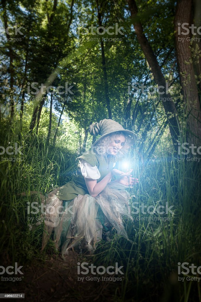 Forest Nymph Holding Magical Firefly in Hand stock photo