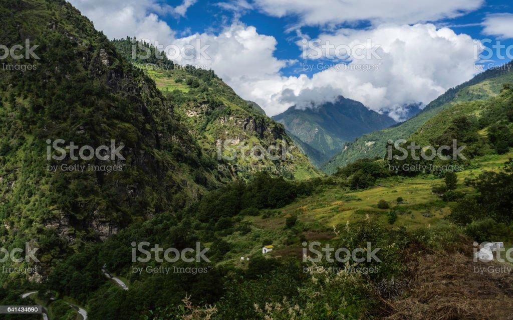 Forested slopes of Himalayas and dwellings, Arunachal Pradesh, India. stock photo