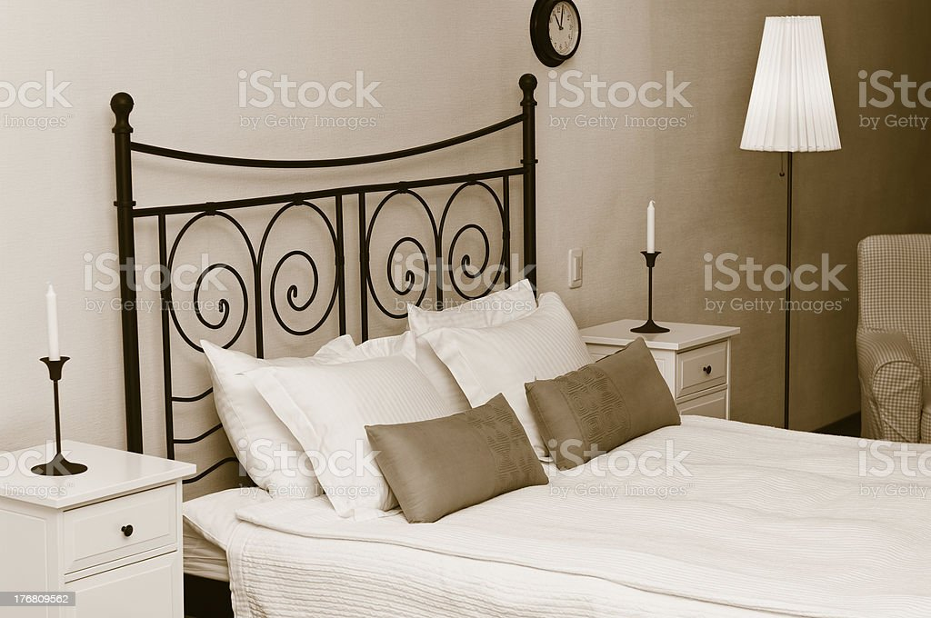Forged headboard of bed with pillows and a white coverlet. stock photo