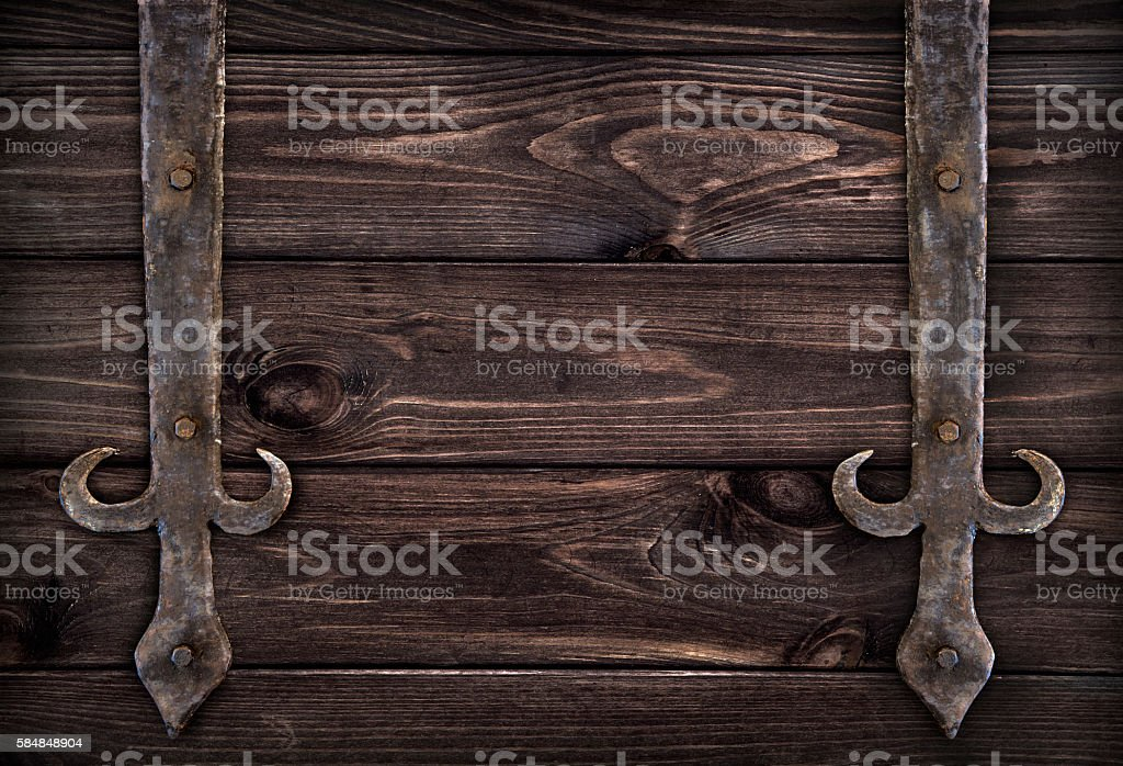 Forged metal elements on dark wooden doors stock photo