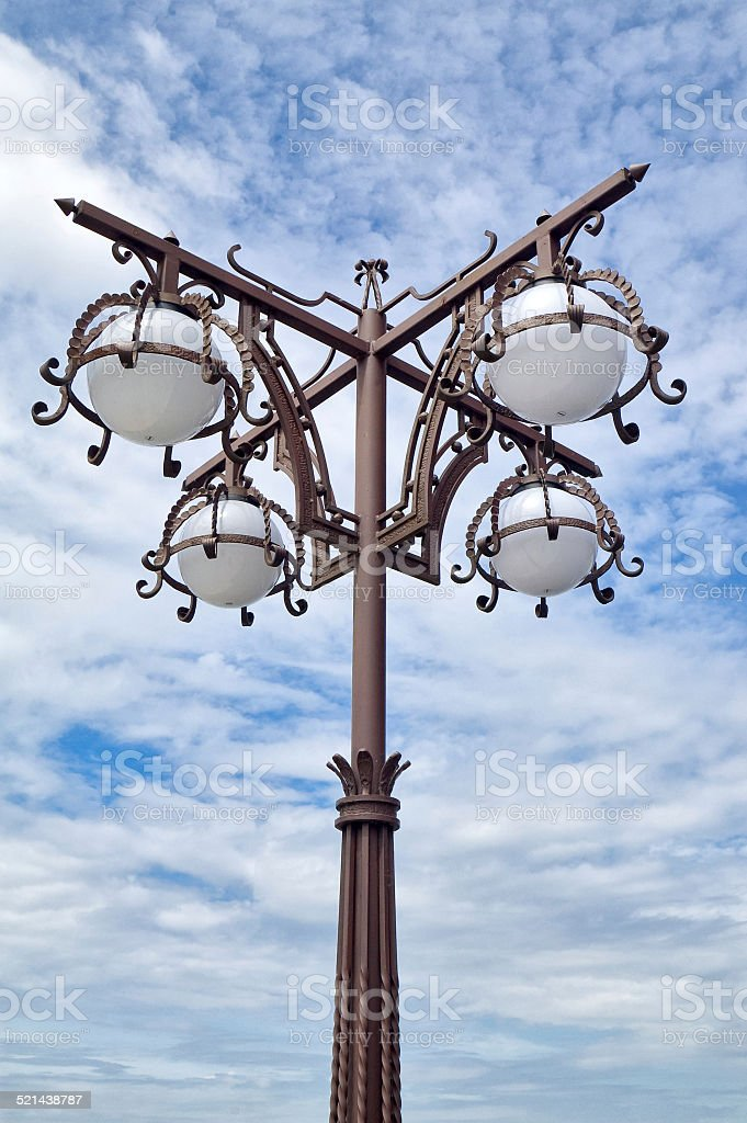 Forged street light and blue sky. stock photo