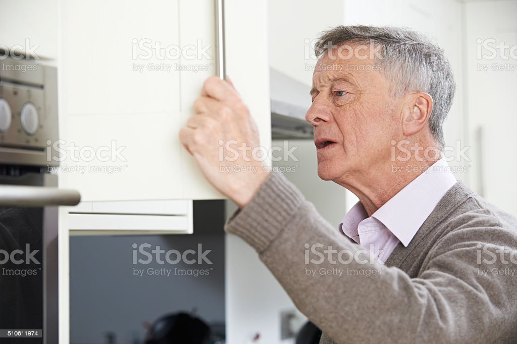 Forgetful Senior Man Looking In Cupboard stock photo