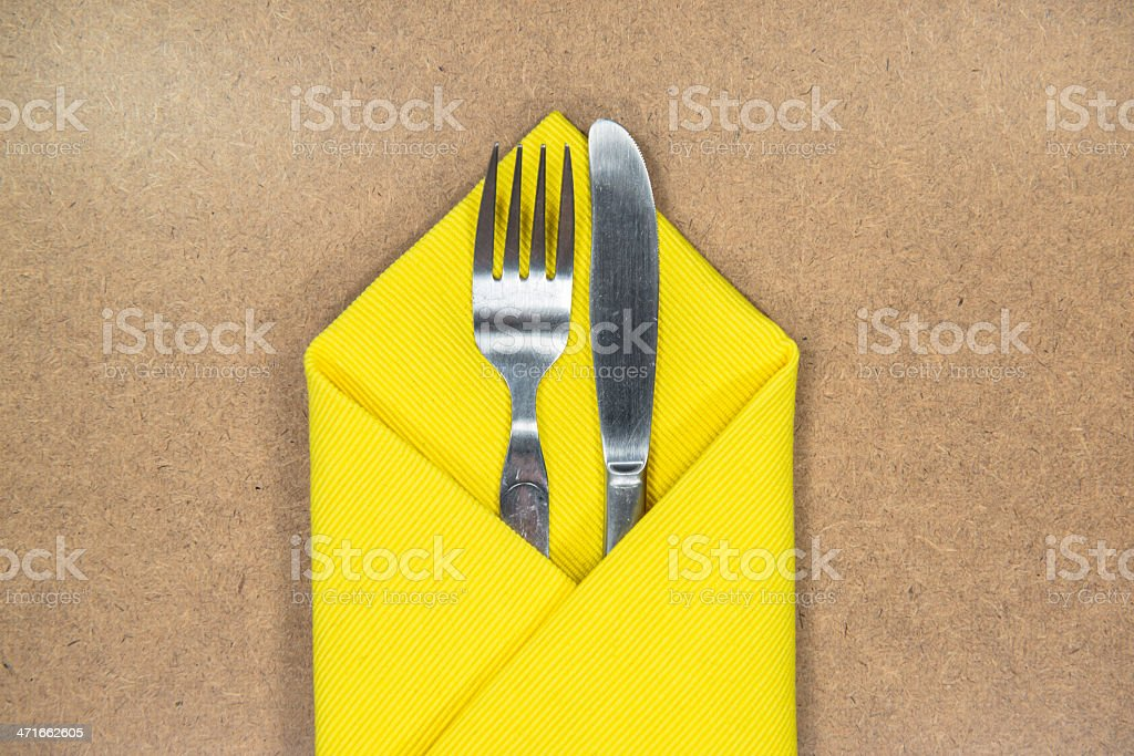 fork and knife in yellow napkin royalty-free stock photo