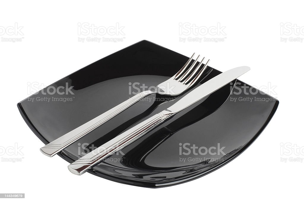 Fork and knife on a black plate. royalty-free stock photo