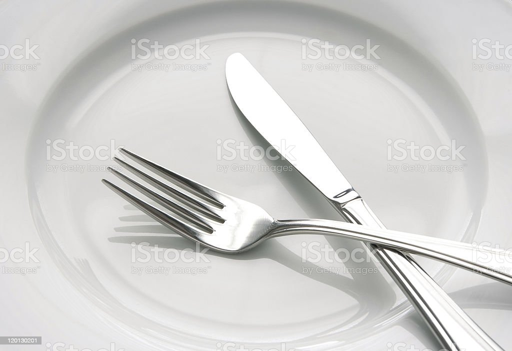 Fork and knife on a white plate royalty-free stock photo