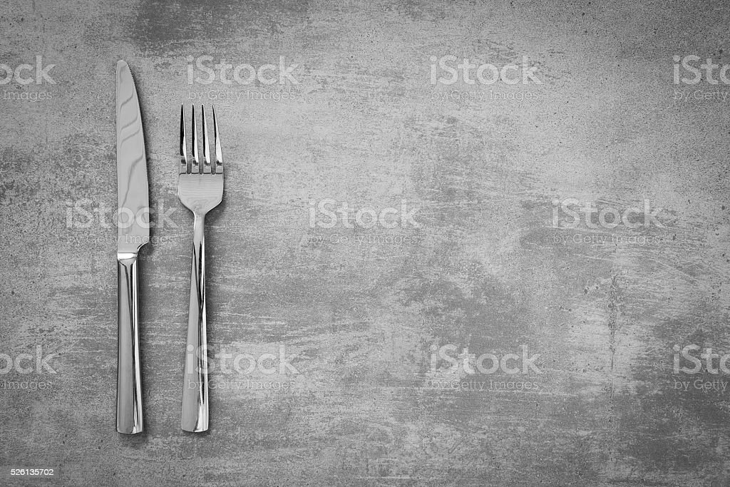 Fork and knife on concrete background stock photo