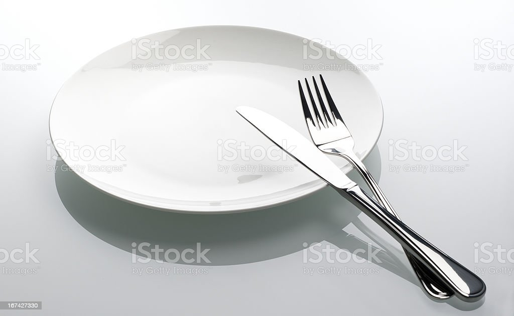 fork and knife on empty white plate royalty-free stock photo
