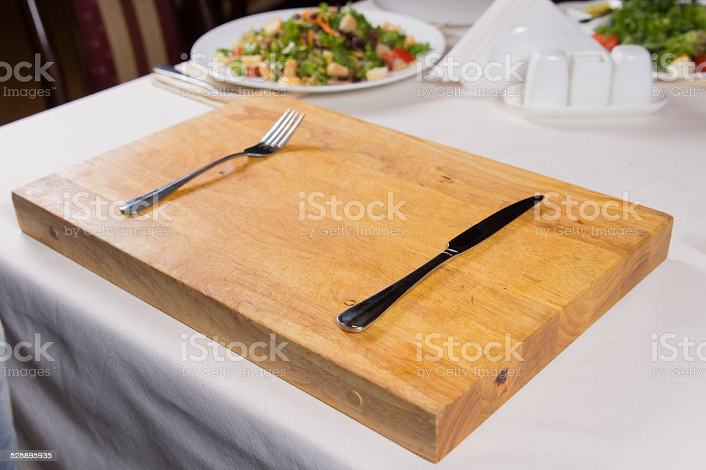 Fork and Knife on Wooden Chopping Board stock photo