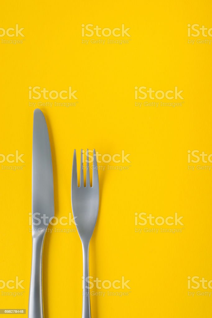 Fork and knife on yellow background, sparse composition with copy space. stock photo