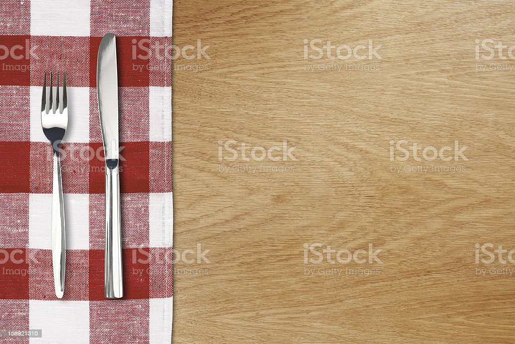 Fork and tableknife on red gingham tablecloth. Wooden table top stock photo