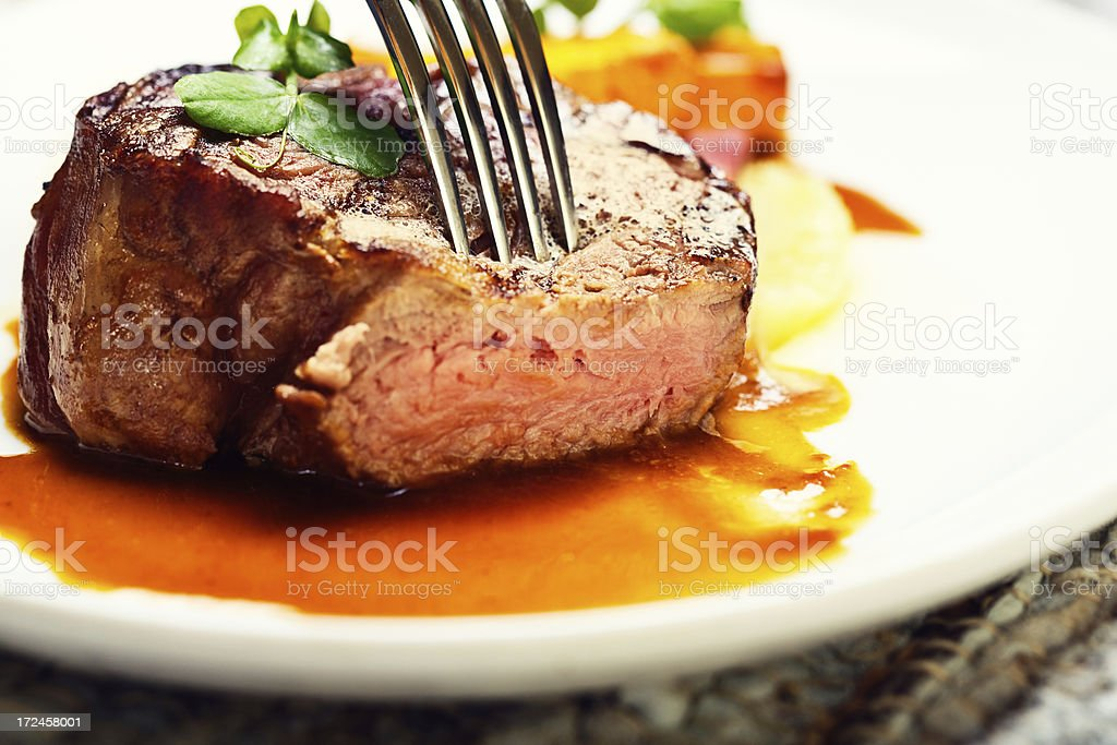 Fork checking tenderness of delicious-looking grilled steak stock photo
