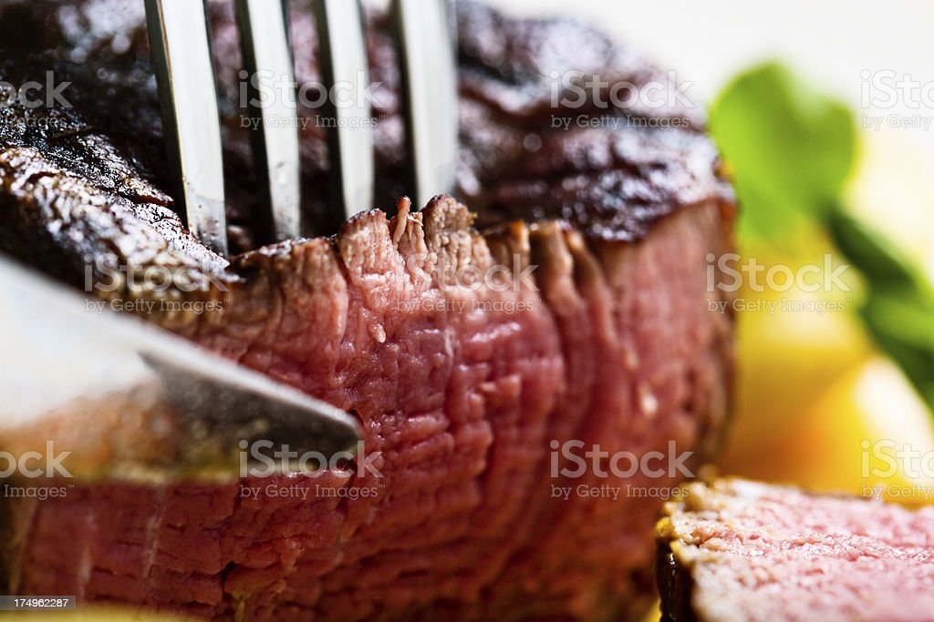 Fork easily piercing tender grilled filet mignon stock photo