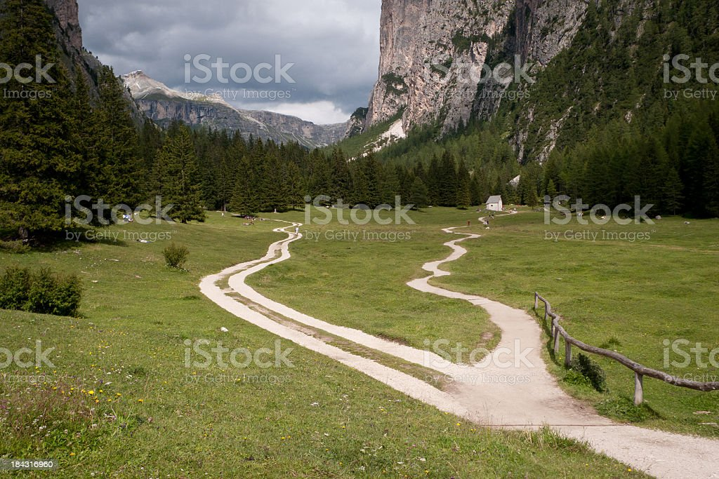 Fork in a path through a mountain valley on cloudy day stock photo