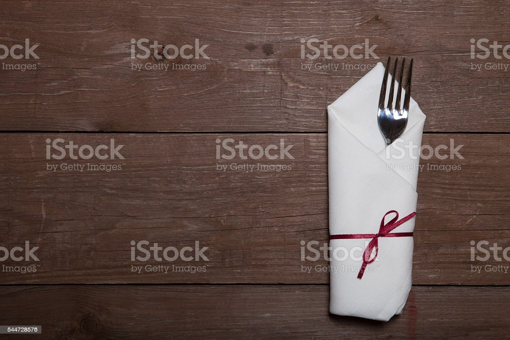Fork in napkin on wooden background stock photo