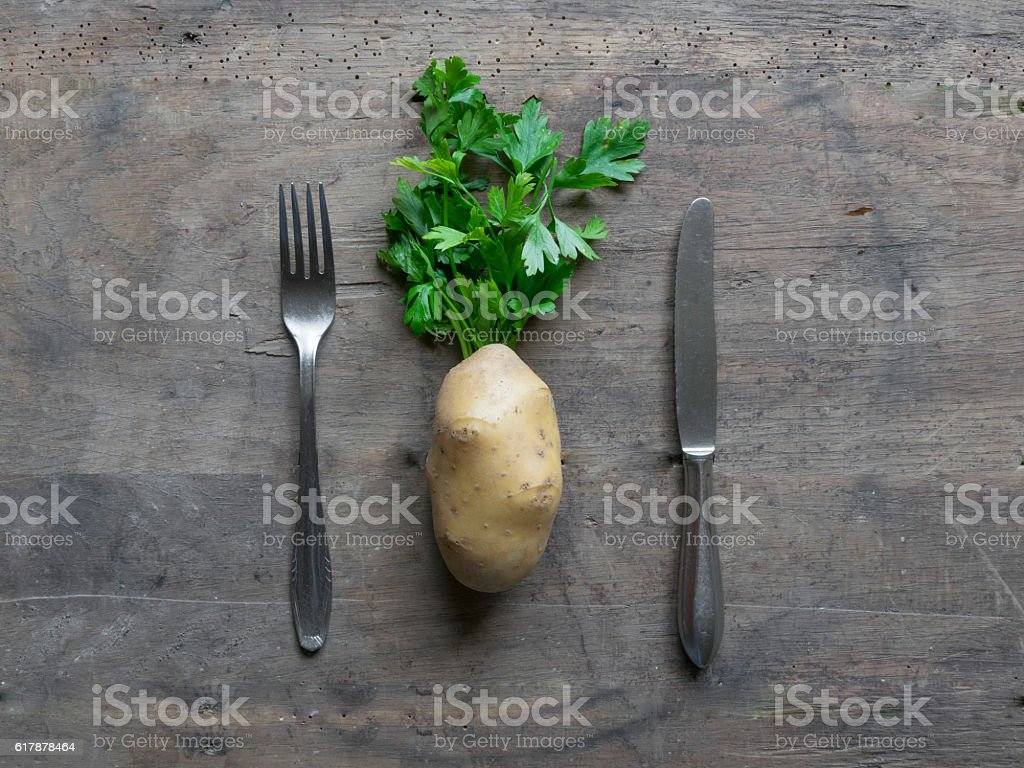 Fork, knife and potato on wooden background. stock photo