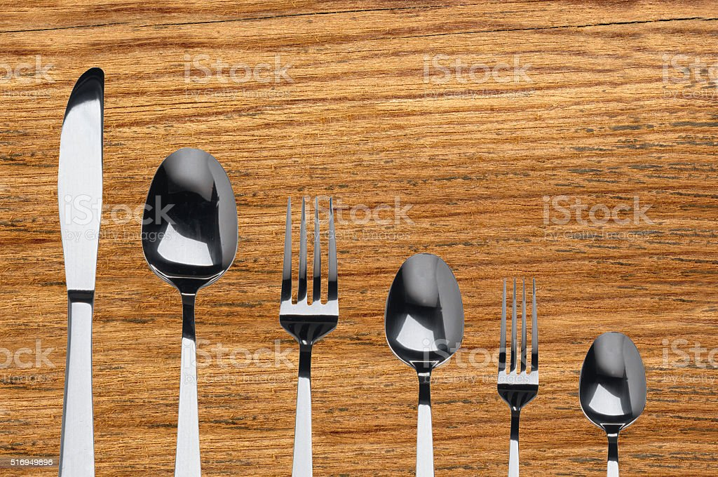 fork ,knife and spoon on wooden background stock photo