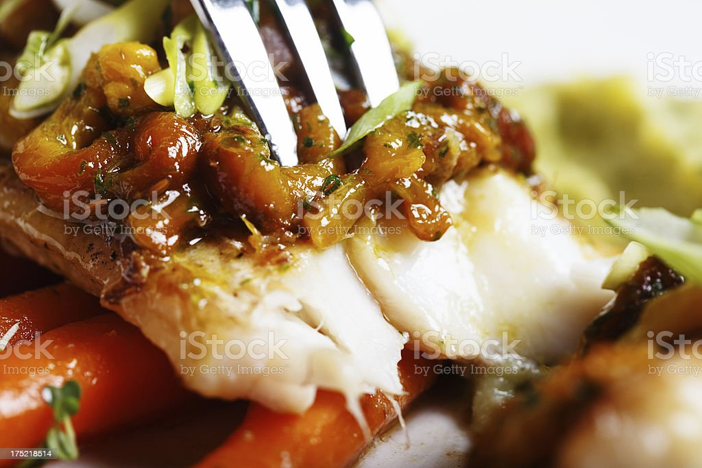 Fork pierces grilled fish and vegetable puree in luxury restaurant stock photo