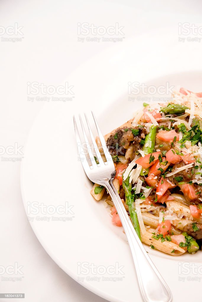 A fork resting on the side of a plate of food  royalty-free stock photo