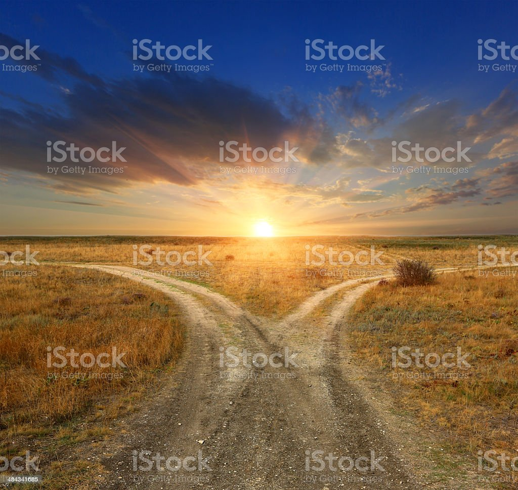 Fork roads on sunset background stock photo