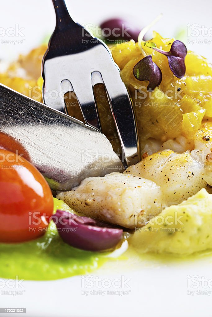 Fork slicing tender grilled fish entree stock photo