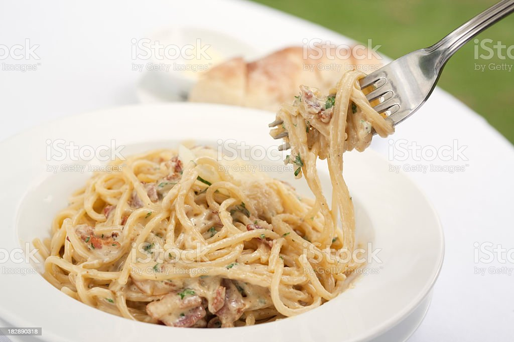 A fork spindles from a bowl of linguine carbonara  stock photo