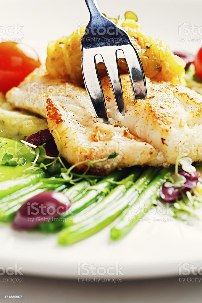 Fork  taking slice of delicate grilled fish dish stock photo