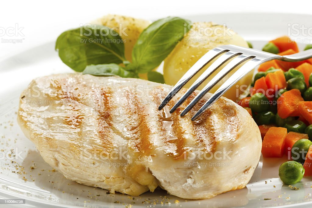 Fork touching a piece of grilled meat next to vegetable royalty-free stock photo