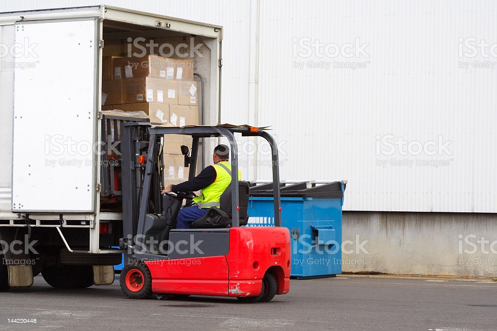A forklift driver loading a truck stock photo