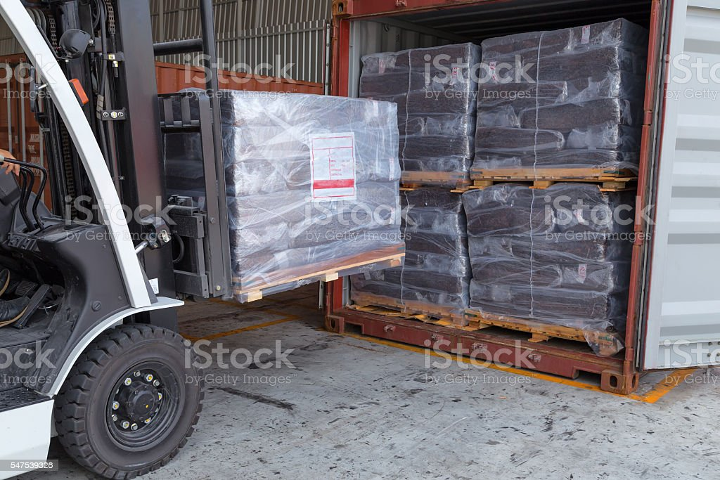 Forklift driver stacking of rubber briquette packs stock photo