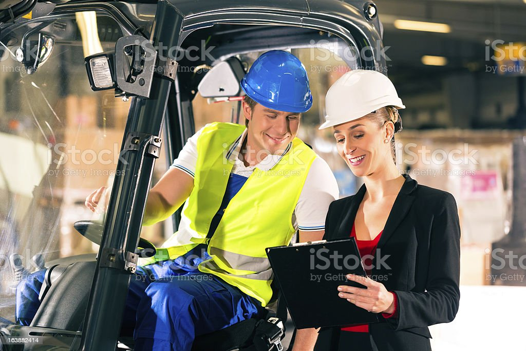 A forklift driver talking to a manager in the warehouse stock photo