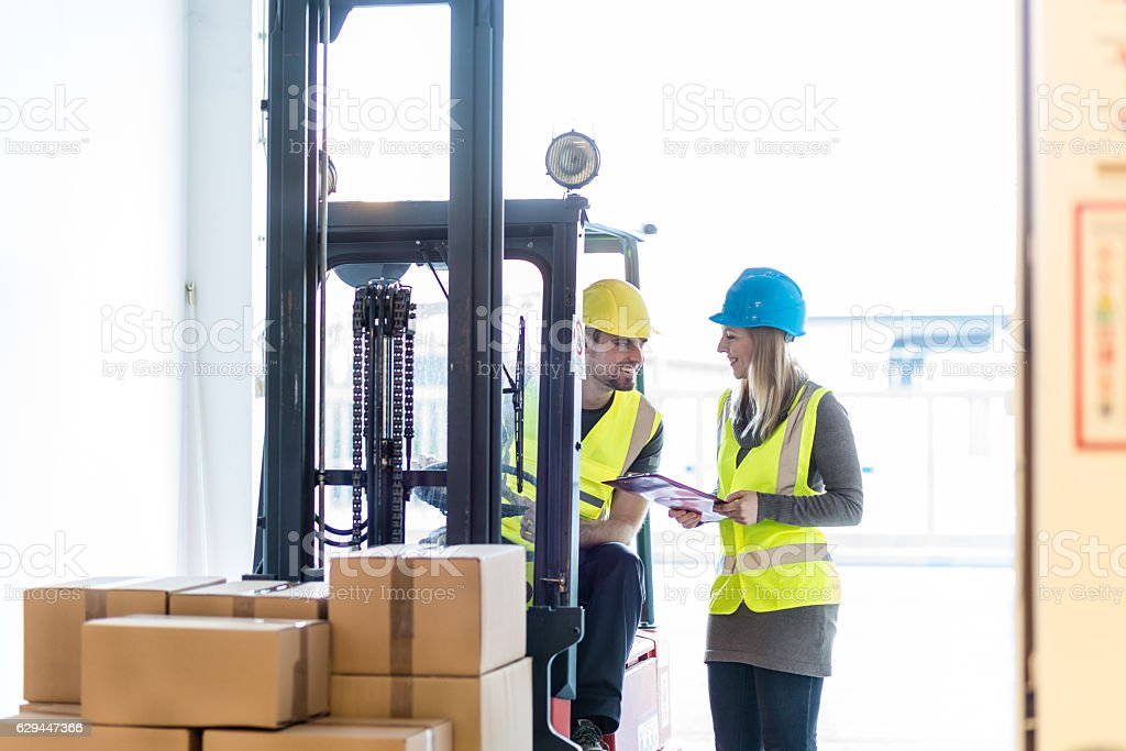 Forklift driver talking to a manager in the warehouse stock photo
