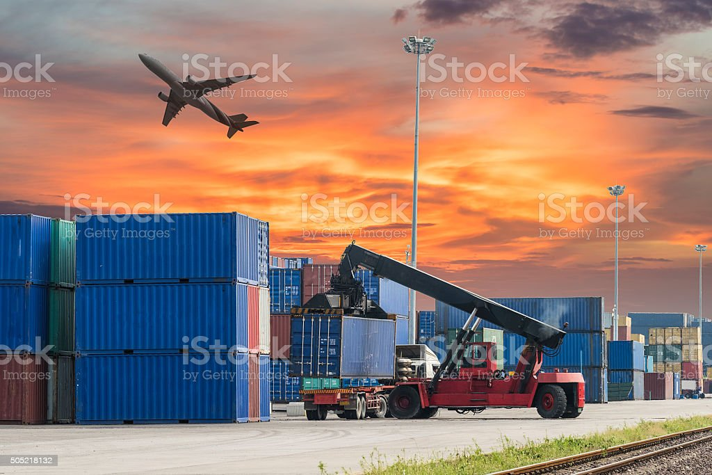forklift handling the container box in logistic zone with sunset stock photo