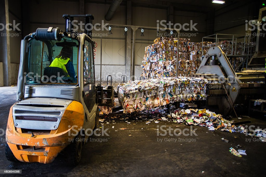 Forklift in the garbage dump with female driver stock photo