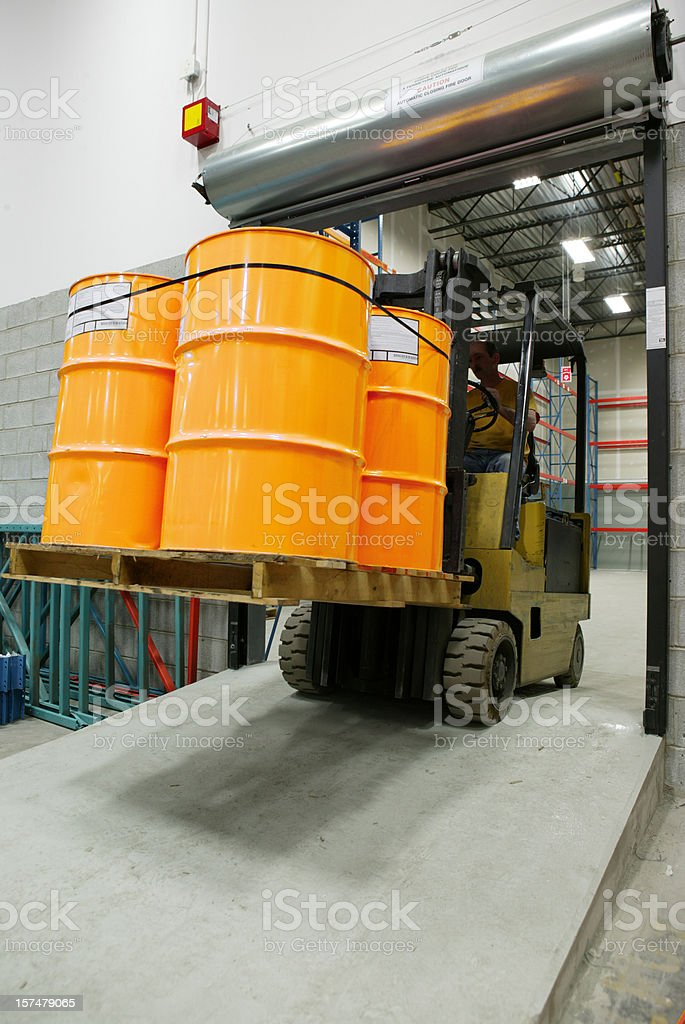 forklift in warehouse carrying yellow barrel stock photo