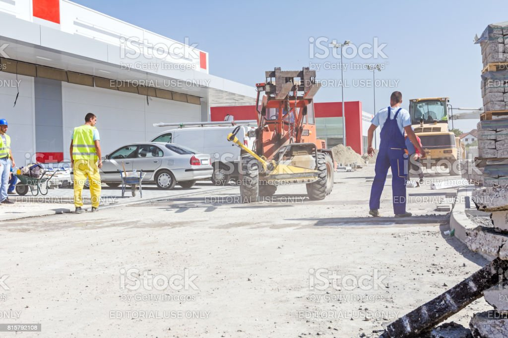 Forklift is carry vibration plate compactor machine at building site stock photo