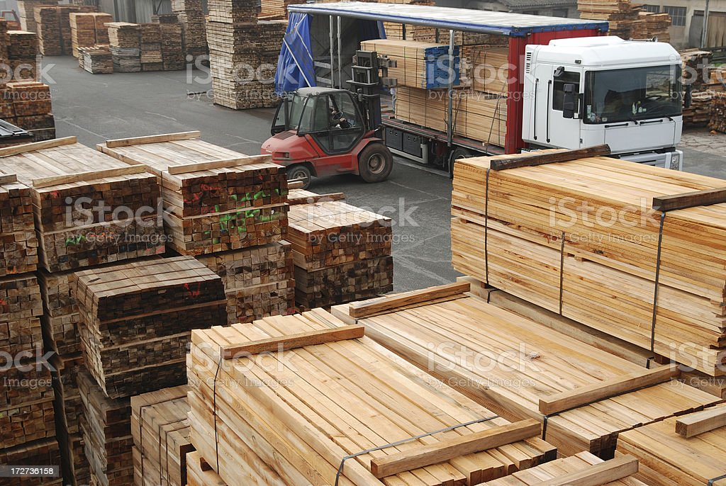 Forklift loading boards in a lumberyard royalty-free stock photo