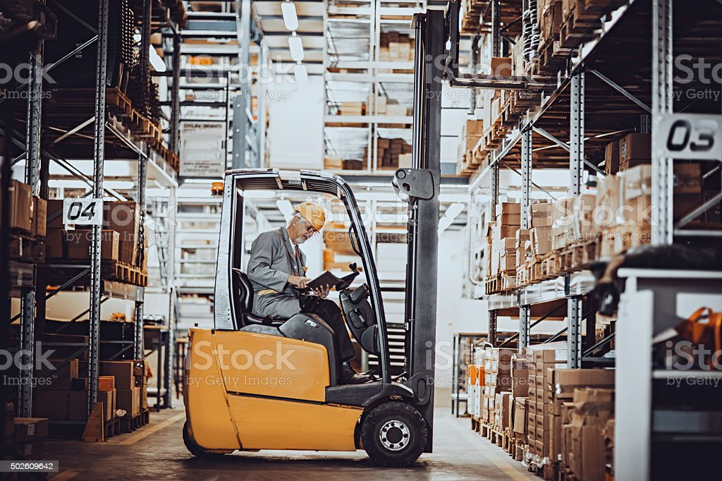 forklift operator at warehouse stock photo