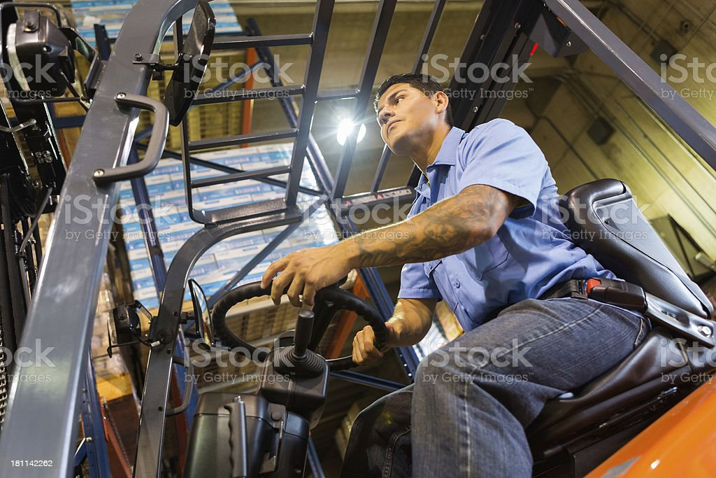 Forklift operator driving machine in warehouse royalty-free stock photo
