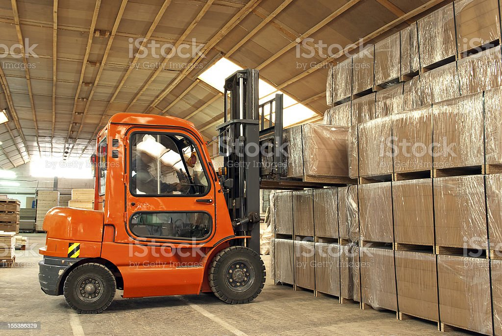 Forklift operator loading boxes in warehouse stock photo