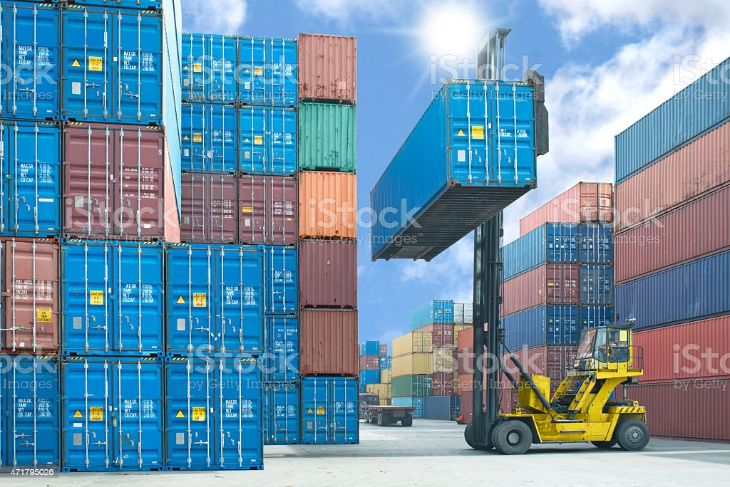 Forklift operator stacking shipping containers in the dock stock photo