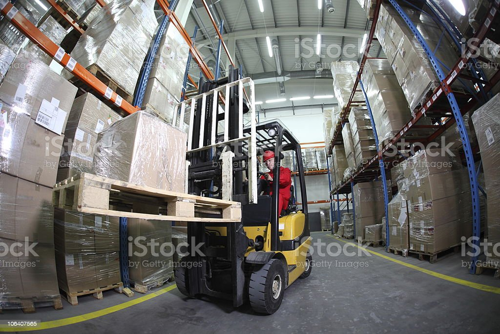 A forklift operator working hard at the warehouse one day  stock photo