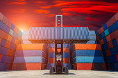 Forklift truck lifting cargo container in shipping yard