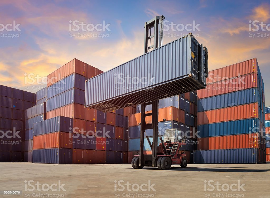 Forklift truck lifting Cargo containers in shipping yard for imp stock photo