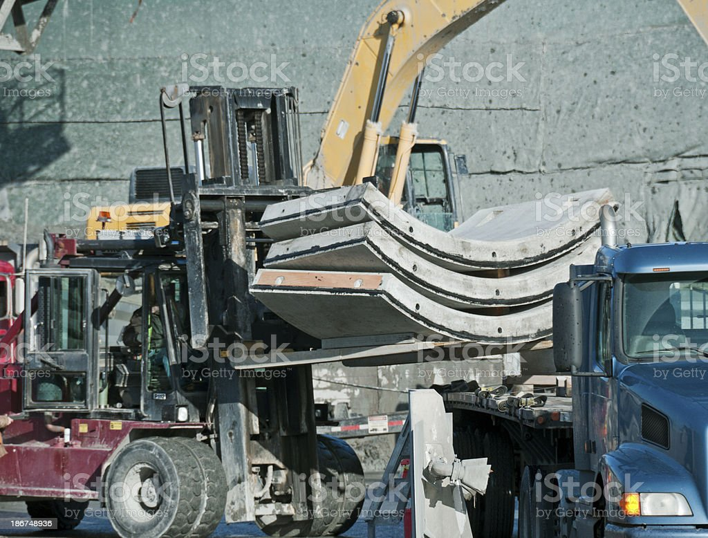 Forklift unloading concrete forms from truck trailer royalty-free stock photo