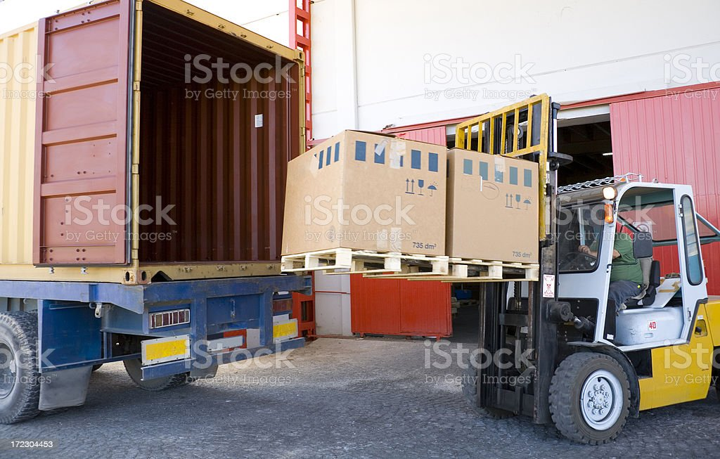 Forklift with boxes by open truck stock photo