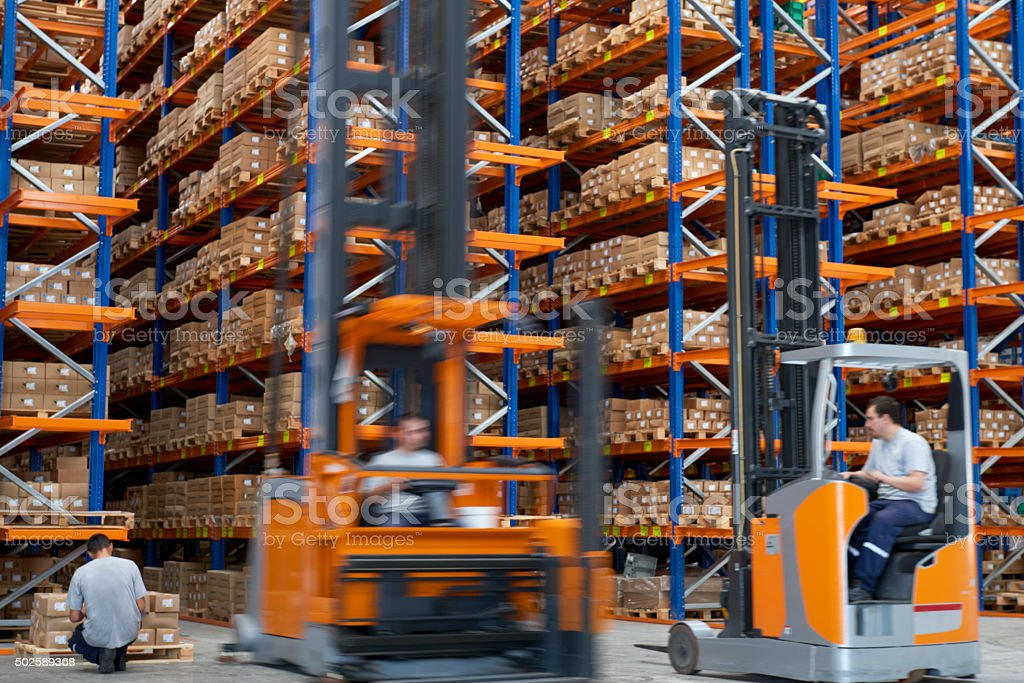 Forklifts carrying cardboard box in warehouse. stock photo