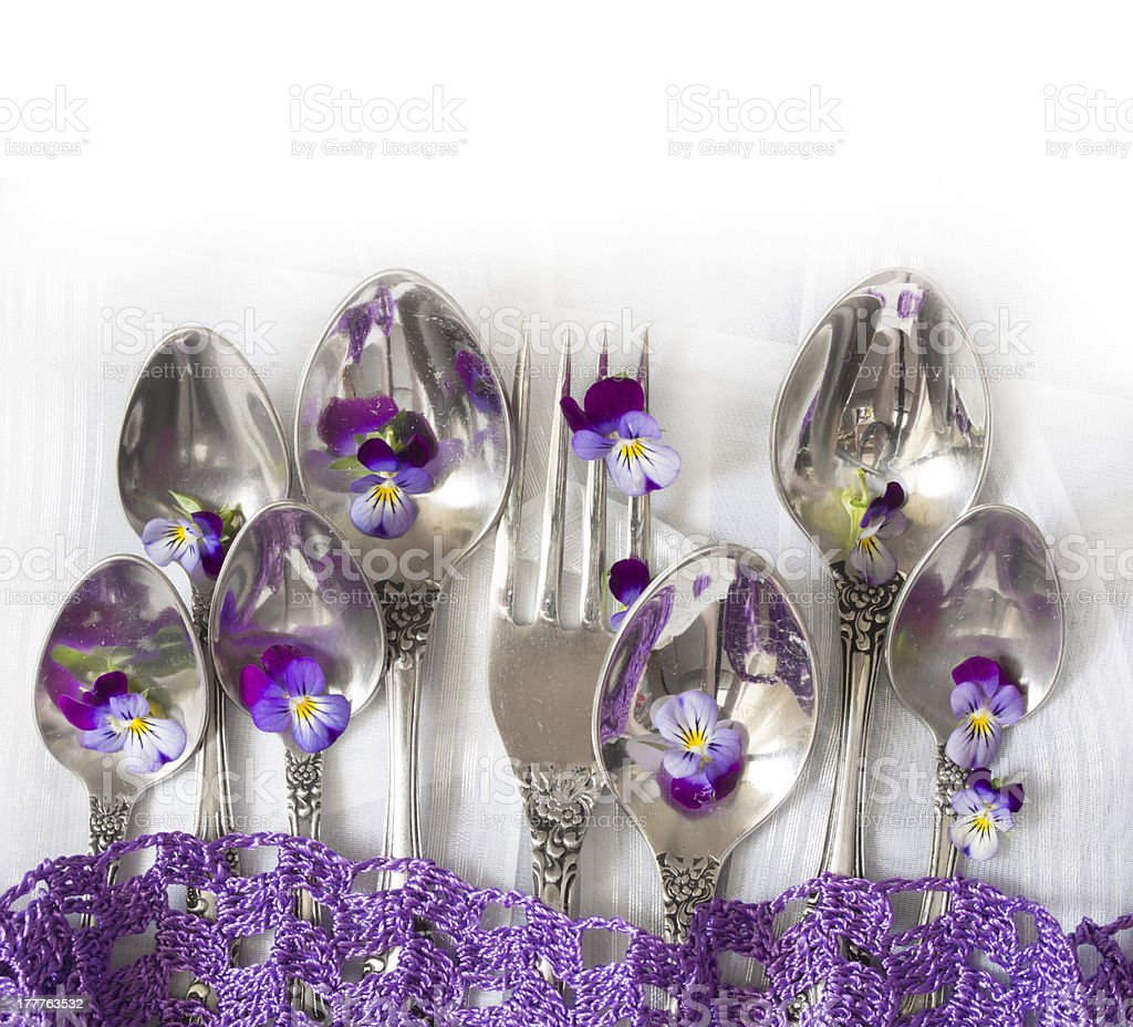 forks and spoons with violets royalty-free stock photo