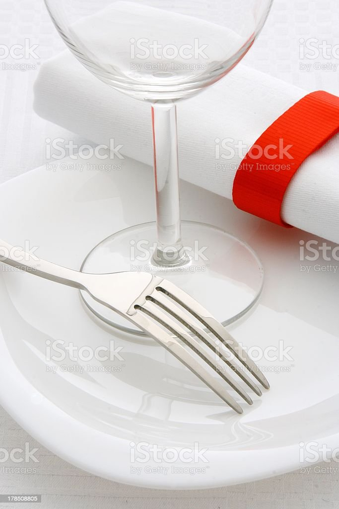 Forks and wine glass on a white plate royalty-free stock photo