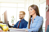 Formal businesswoman in office with businessman writing EU project proposal