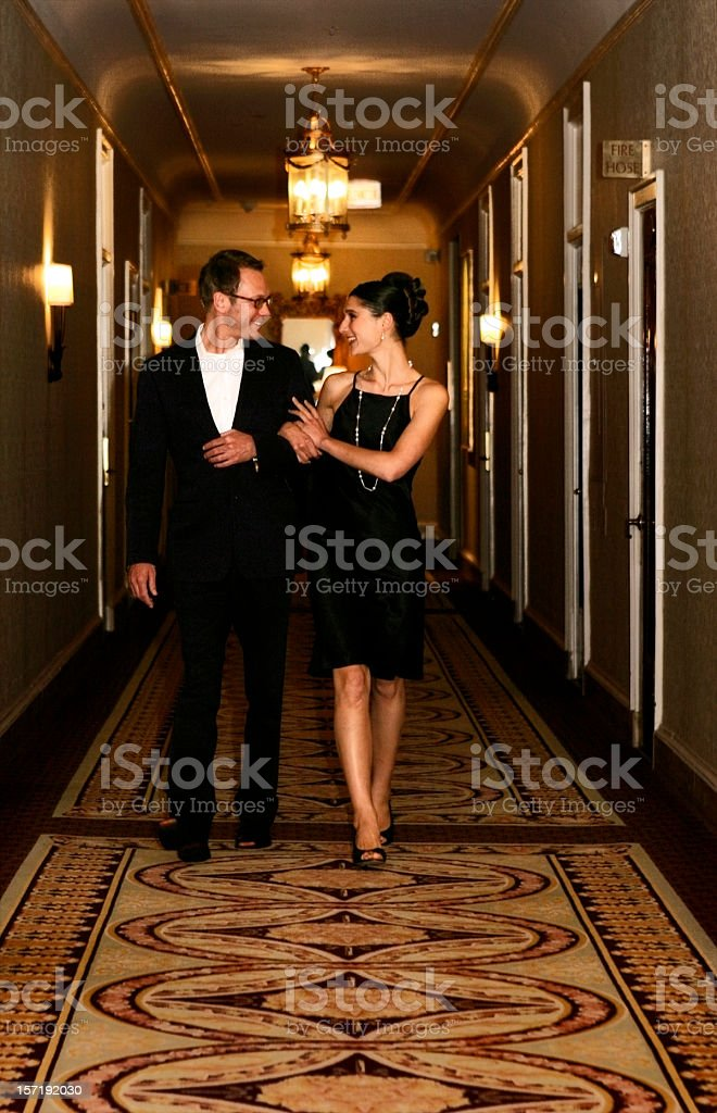 Formal couple walking down hall with arms interlocked  stock photo